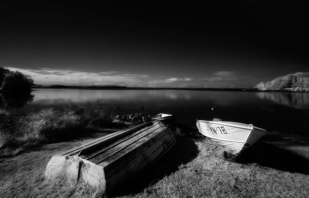 Heavenly view showing boats at Wallis Lake,  NSW, Australia.  View of upside boats on calm lake. Scenic view of boats on shore of Lake Wallis. Black and white photograph.