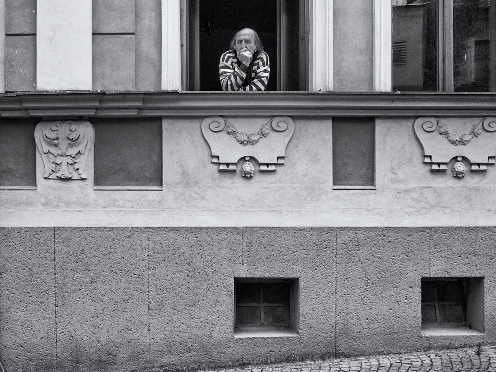 View of an old man looking out from a window in Kutna Hora, Czech Republic