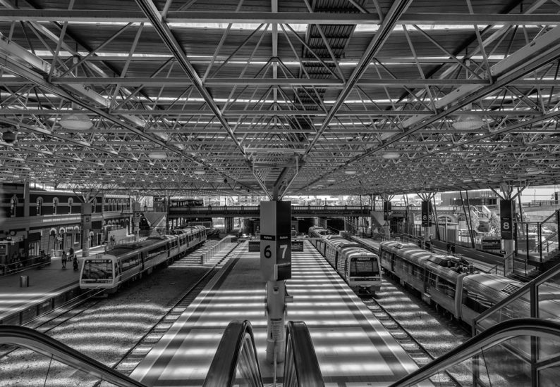 Central station in Perth shows the main hall with trains, platforms and tracks. Western Australia. Trains sitting in Perth train station. Black and white photography.