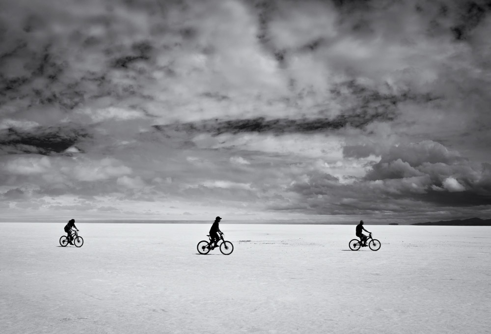 Salar de Uyuni in Bolivia is the biggest salt flat in the world. three friends and their bikes. friends cycling.