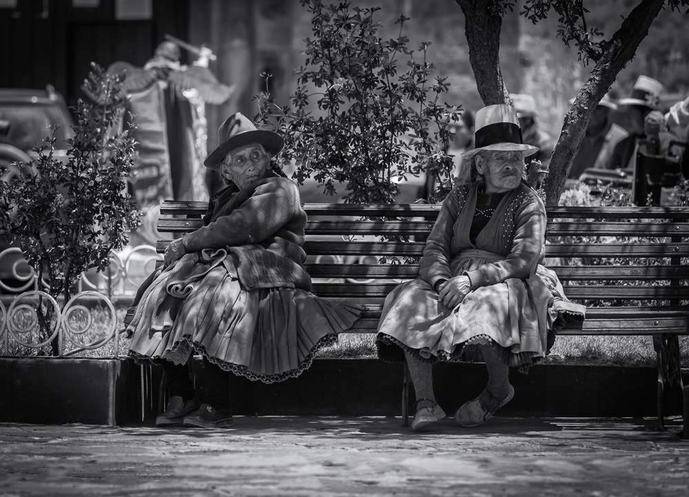 woman, rural and indigenous, wearing traditional Andean clothing.  Women in traditional outfit  sitting on a bench in Downtown Cusco.