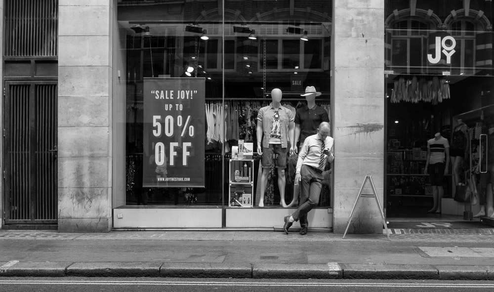 Three wise men in the London shop. A man standing up outside shop looking at his phone. Two mannequins behind the window shop looking at the man. street photography. black and white photography.