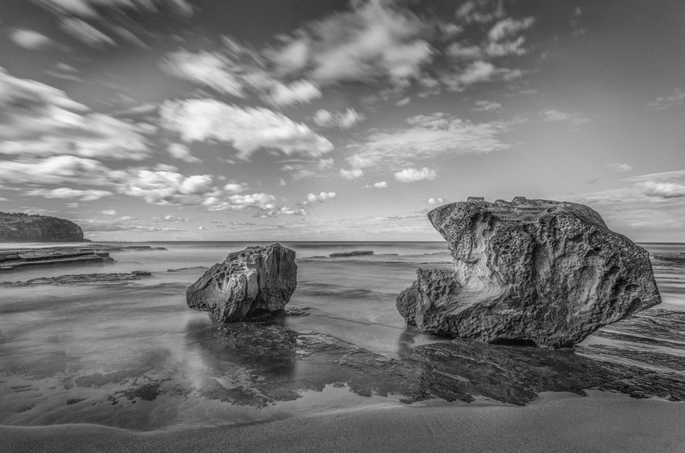 Turimetta Beach in Australia. Big rock formation on the beach. A sunny winter day at the beach. Black and white photography.