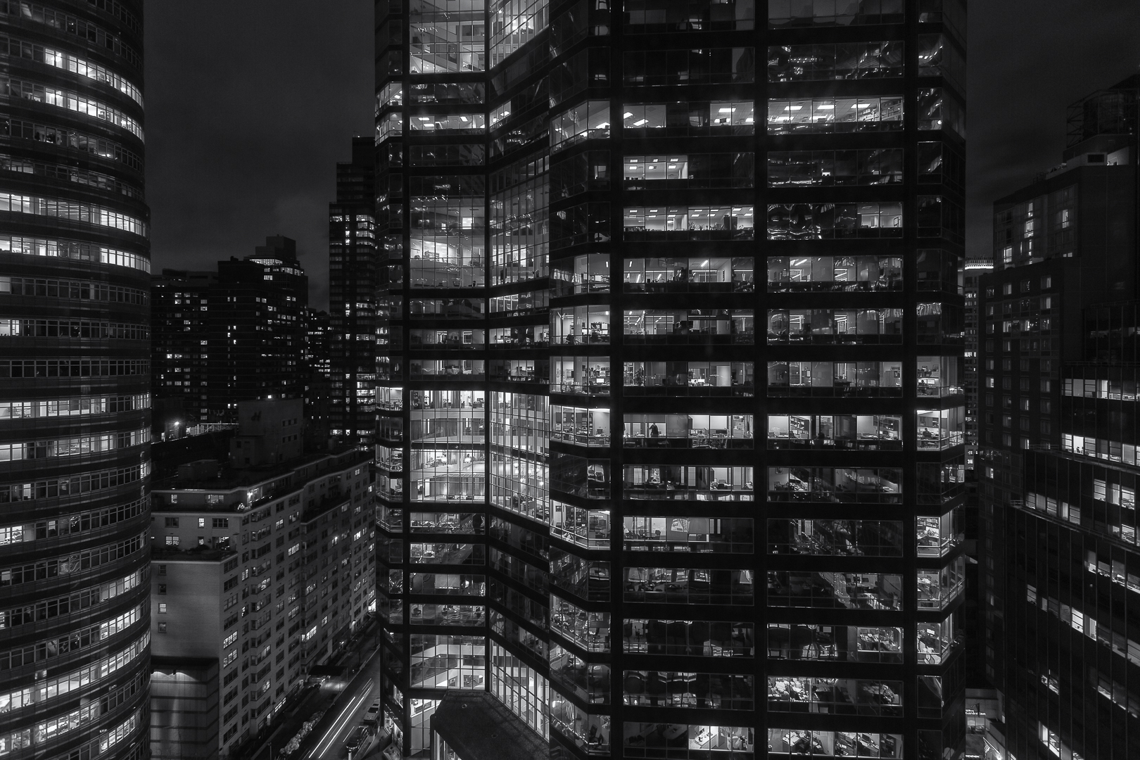 Buildings at night in New York City. Night time exterior view of a building. Buildings with lights on in many windows. Black and white photography.