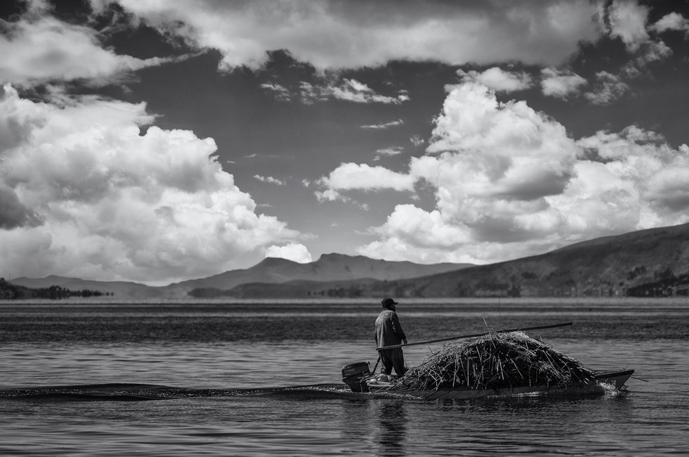 Lake Titicaca in black and white photograph . local man sails Lake Titicaca  by small boat , local  man bringing  reeds on boat.