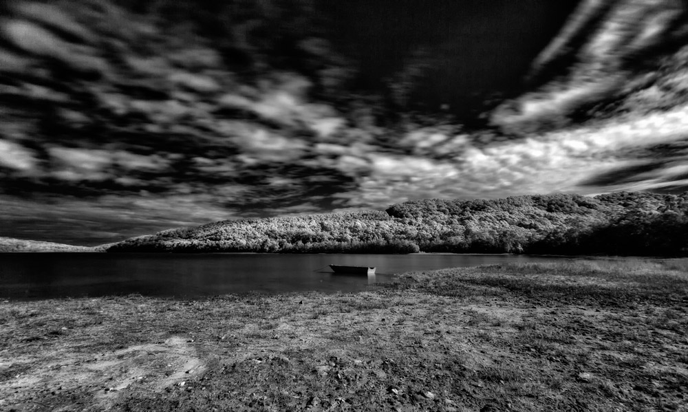 Old and decaying wooden boat. Boat on a lake waiting for adventure.Solitary wooden boat on lake. Black and white photography of a wooden boat on a scenic lake.