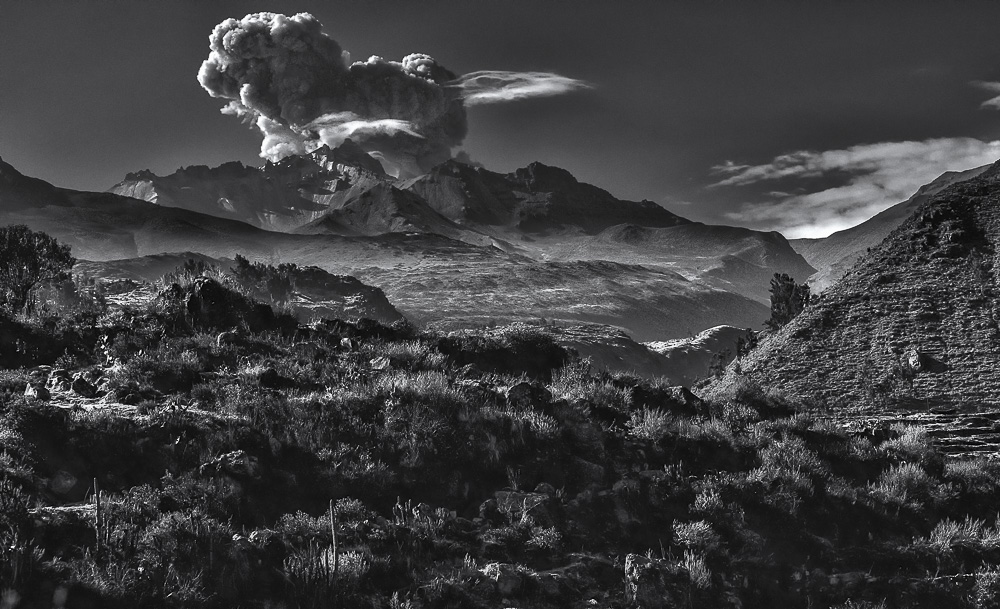 Highlands landscape in Peru. Sunny and hot day in the highlands of Peru. Contrasting black and white landscape scene with mountain and big cloud.