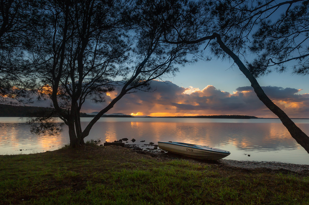 beautiful sunrise over a calm lake with boat on shore, sunrise flame colors in the sky and water