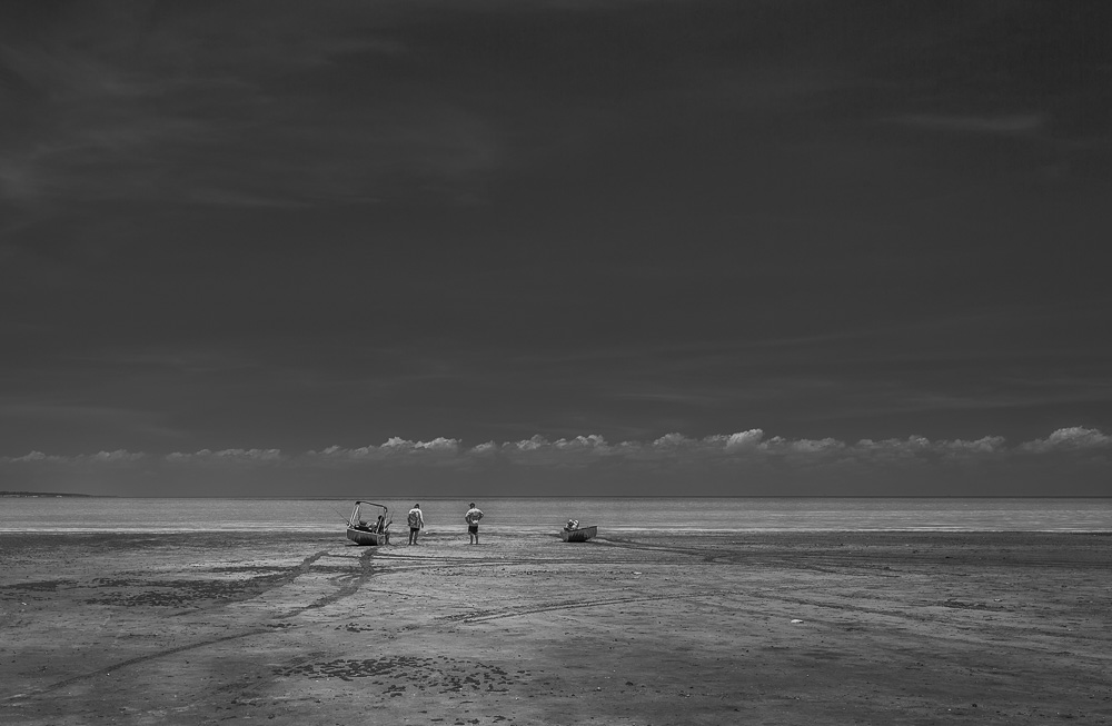 Broome, rear view of two men standing up looking at the ocean. Two men with fishing boats standing at the shore. Black and white photography