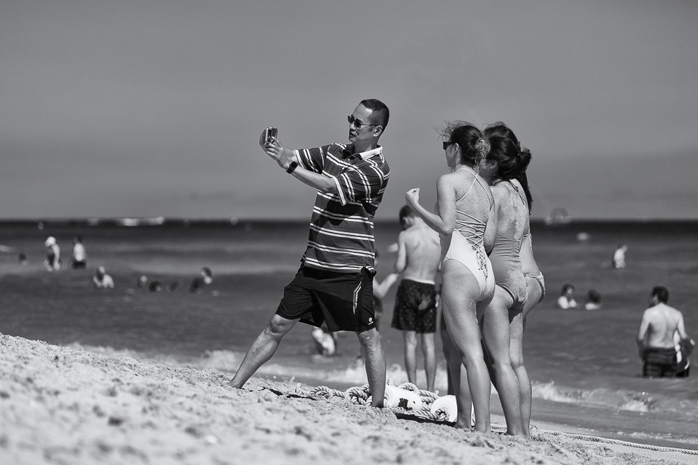Asian man and three young women wearing swimwear taking selfie on beach, Miami Beach