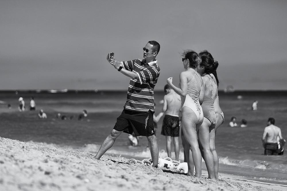 Asian man and three young women wearing swimwear taking selfie on beach, Miami Beach