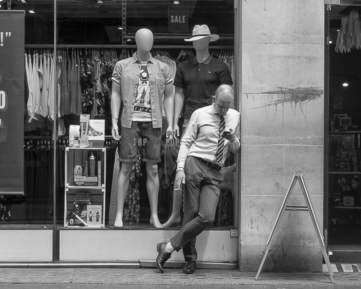 A man standing up outside shop looking at his phone. Two mannequins behind window shop looking at the man.