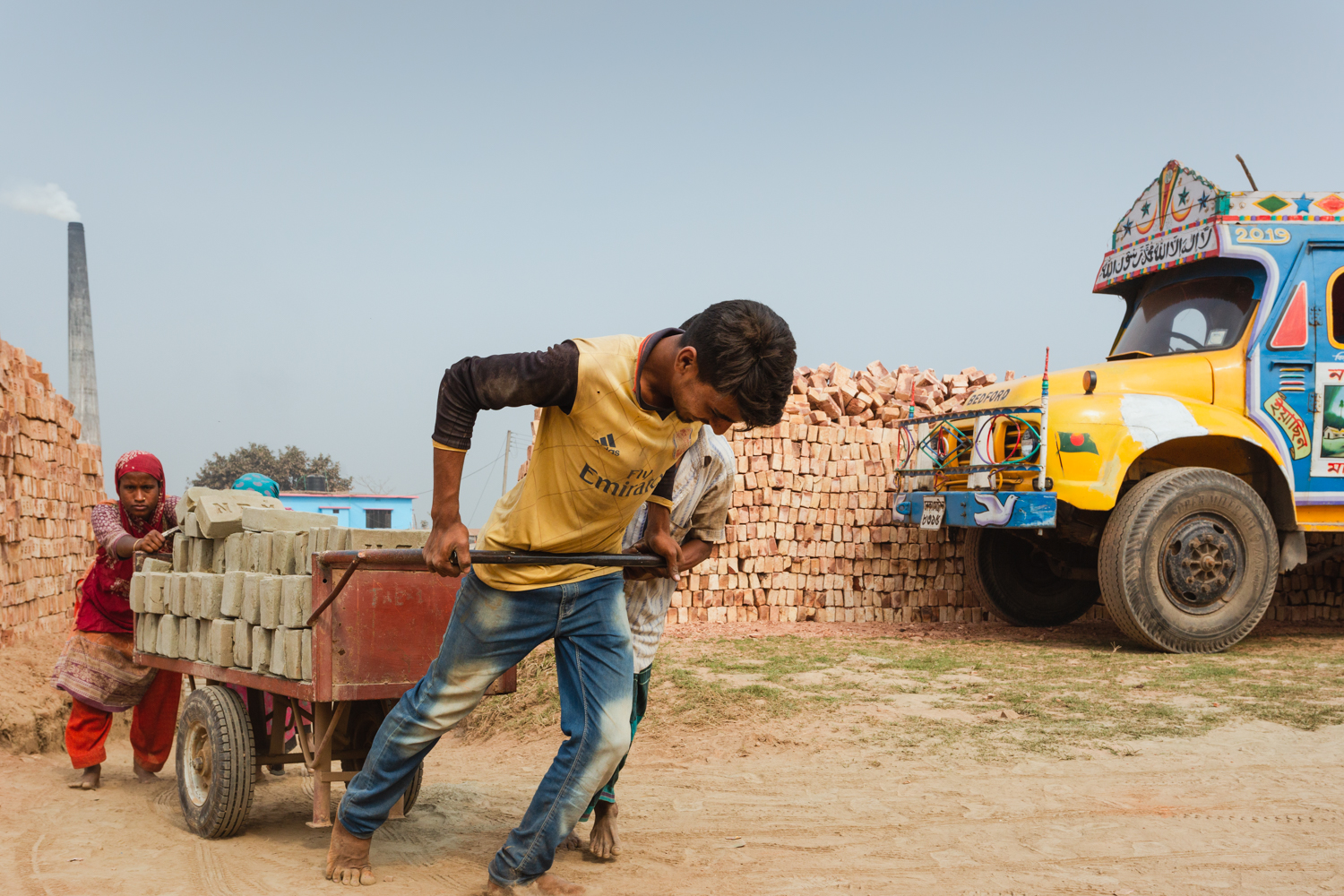 A trolley with a heavy load of bricks pulled uphill by workers in Chittagong, Bangladesh.