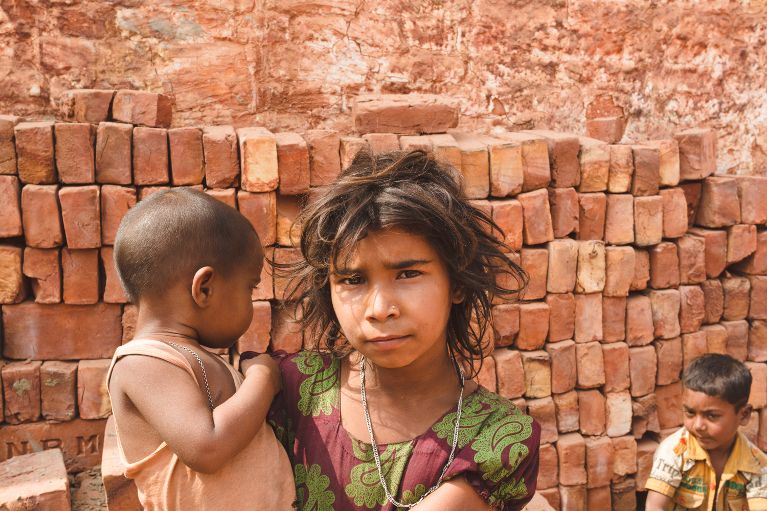 Chittagong, Bangladesh brick worker children caring for the younger sibling.