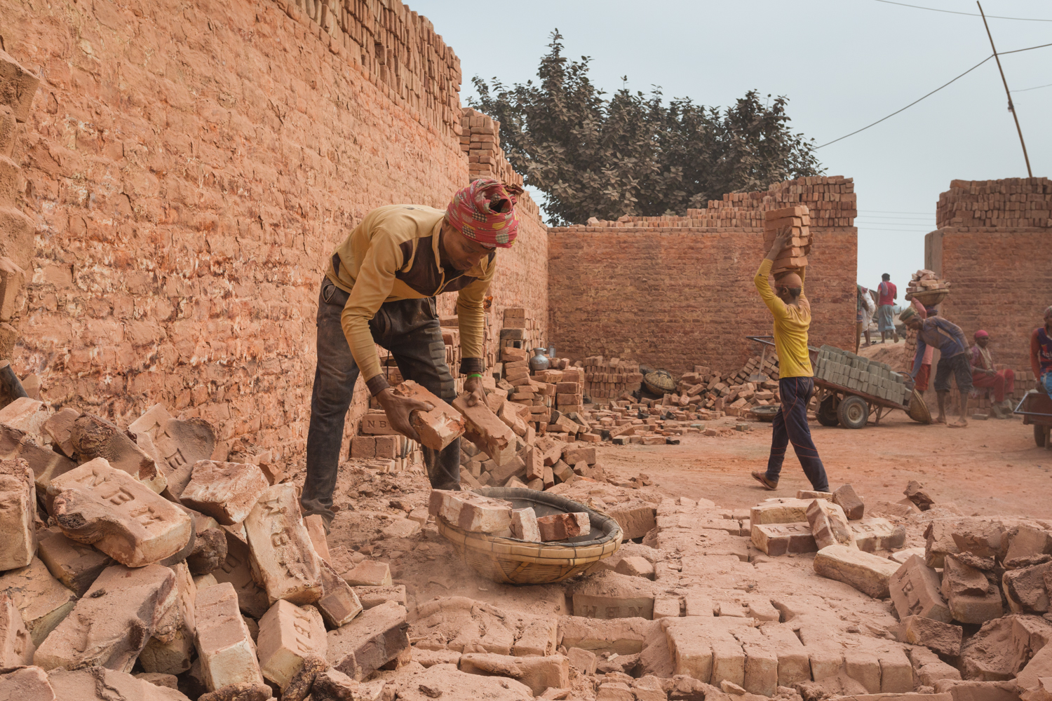 Worker sorting bricks in Chittagong, Bangladesh without protective gear.