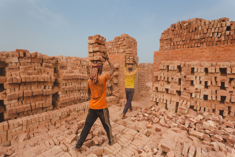 Heavy loads of brick carried by head at the Chittagong, Bangladesh brick facility.