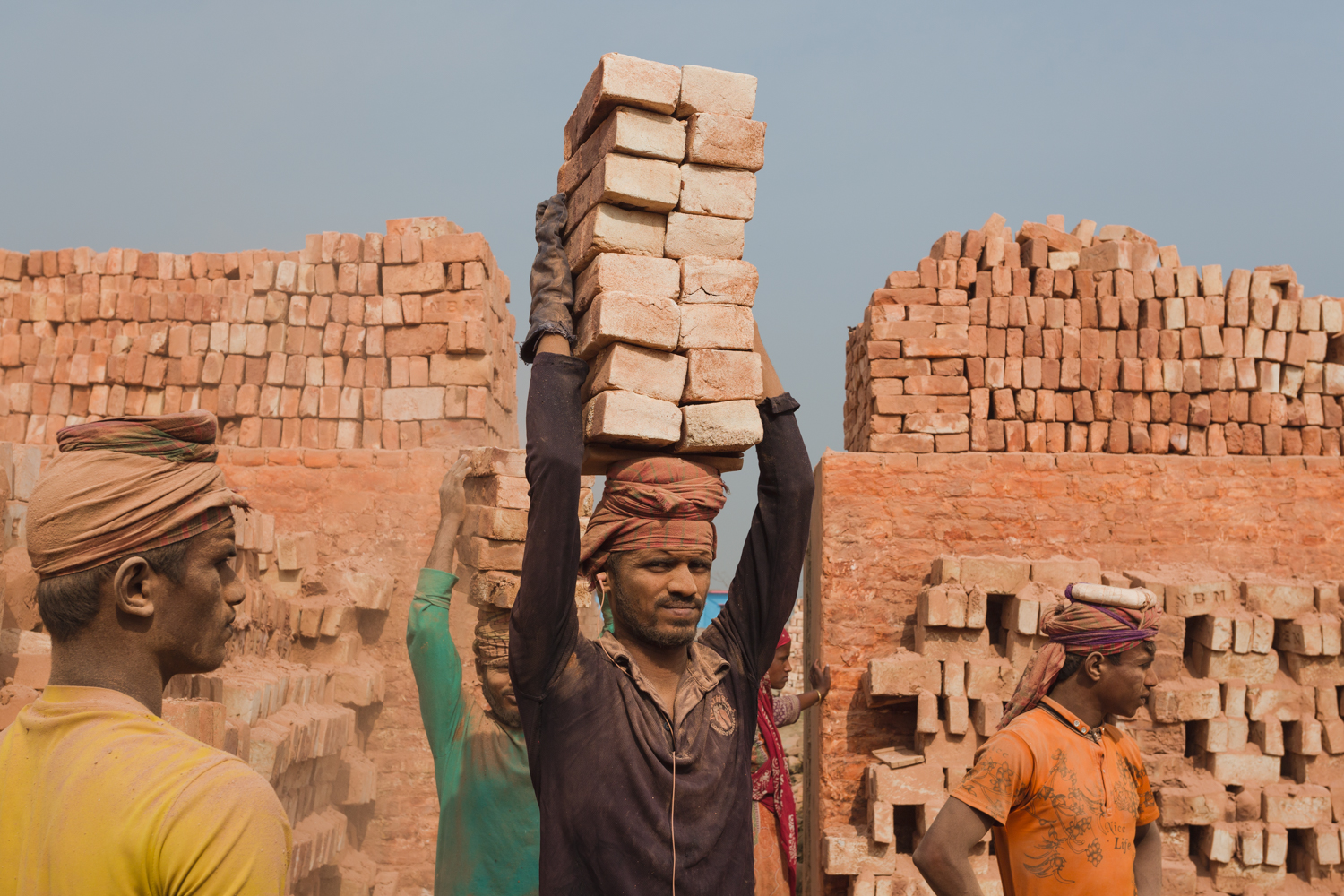 A worker covered by brick dust transporting bricks in Chittagong, Bangladesh.