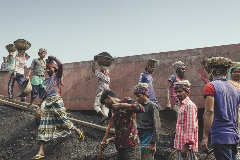 The coal workers at Dhaka, Bangladesh are consistently walking back and forth with loads of coal on their heads.