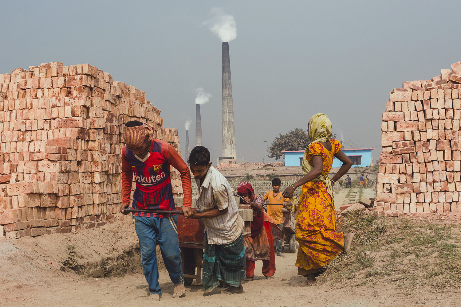 Heavy loads of bricks being pulled up hill by teamwork at the Chittagong, Bangladesh facility.