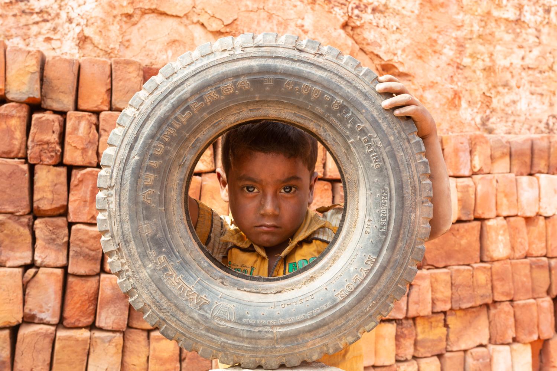 A child with a tyre at the Chittagong, Bangladesh brick facility.