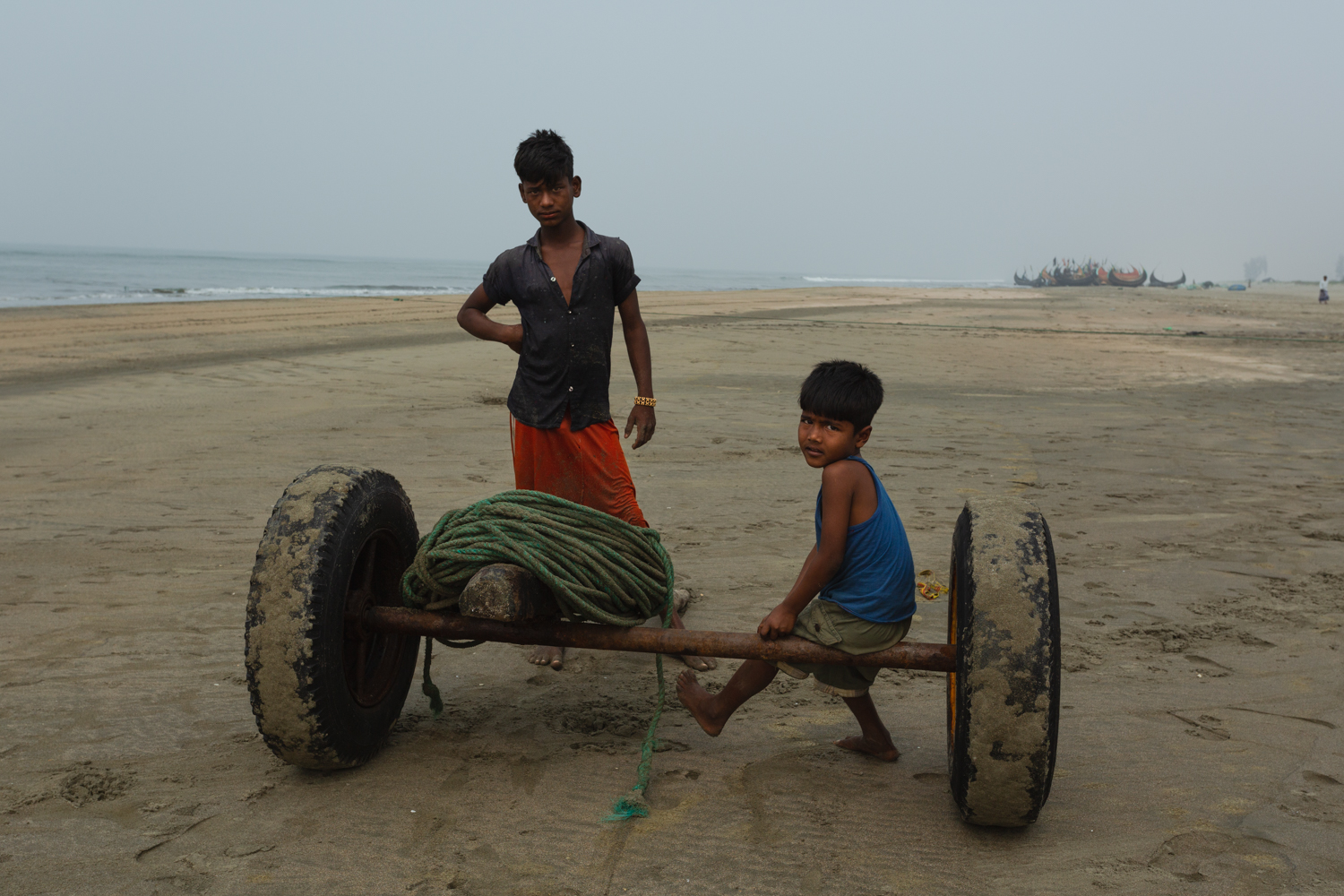 Boys at Bay of Bengal Cox's Bazar Bangladesh wait with boat transport equipment