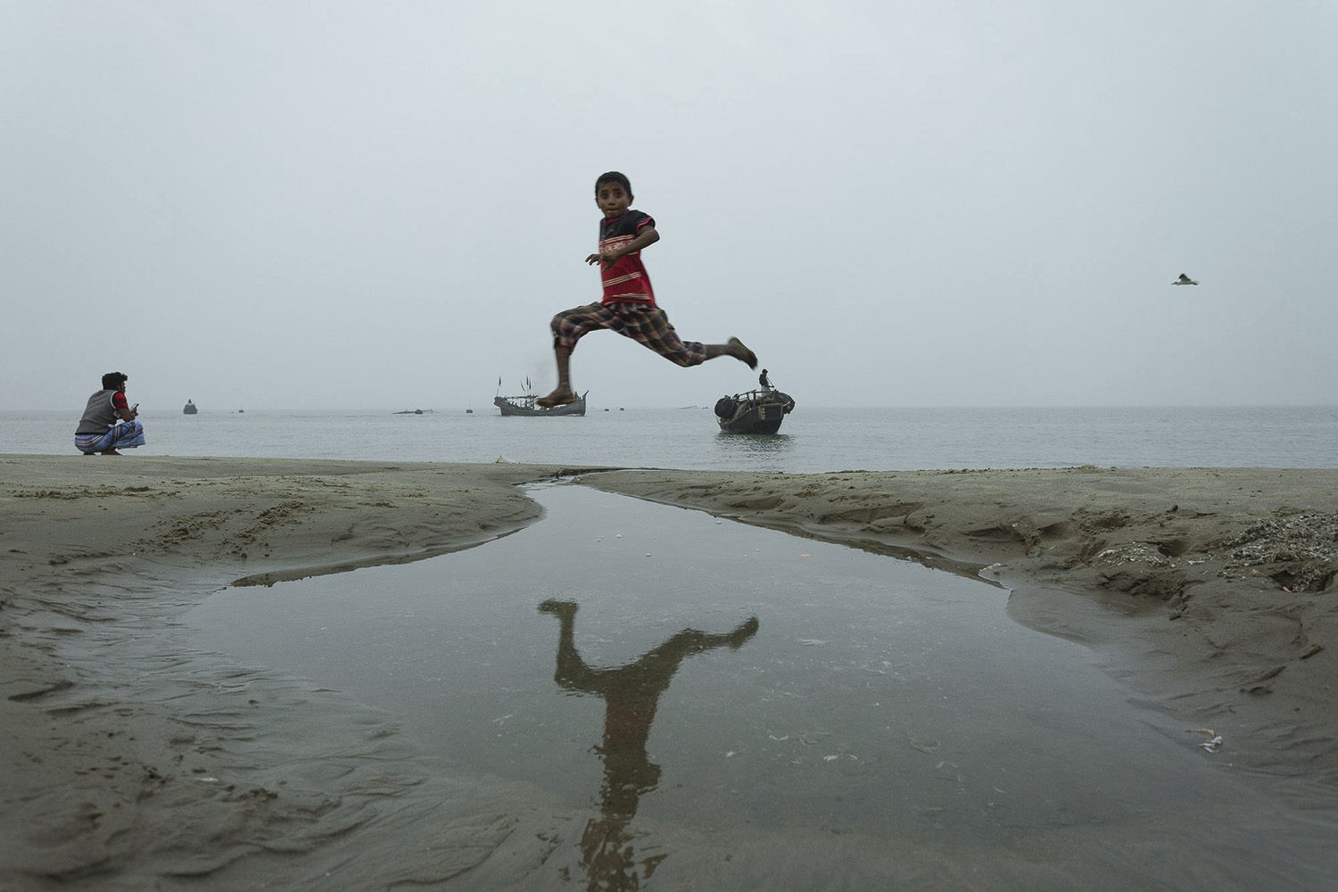 A child leaping over puddles in the sand at  Bay of Bengal, Cox's Bazar Bangladesh