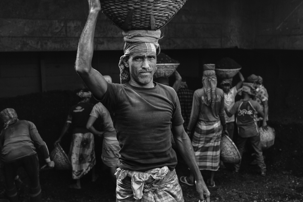 A man carries a heavy basket full of coal on his head in hot conditions at Dhaka, Bangladesh