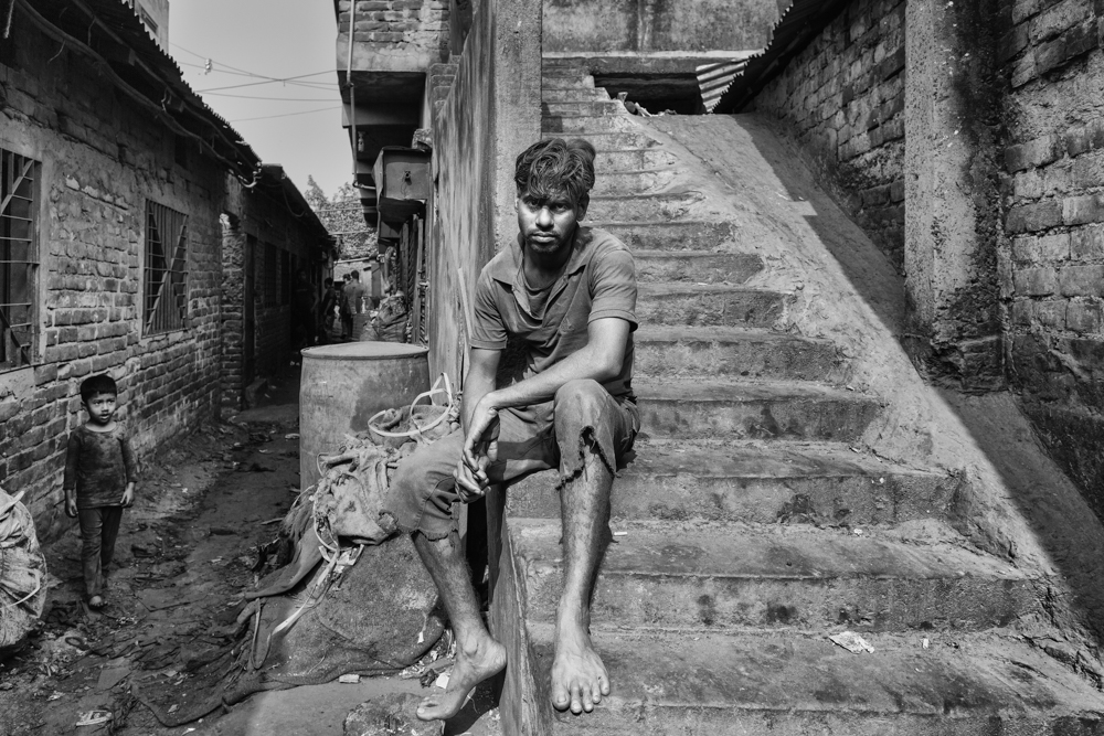 During a break, this aluminium factory labourer sits outside covered in aluminium dust, which is harmful to their health. Dhaka, Bangladesh 2020