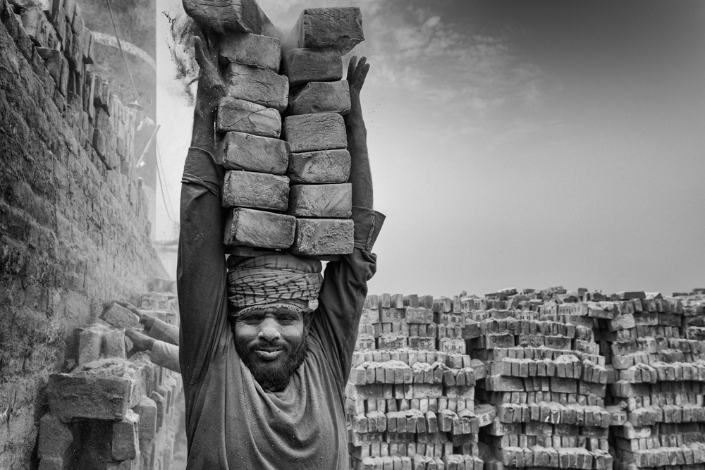 A labourer picks up and carries a heavy load of bricks on his head, covered in thick dust, Bangladesh 2020