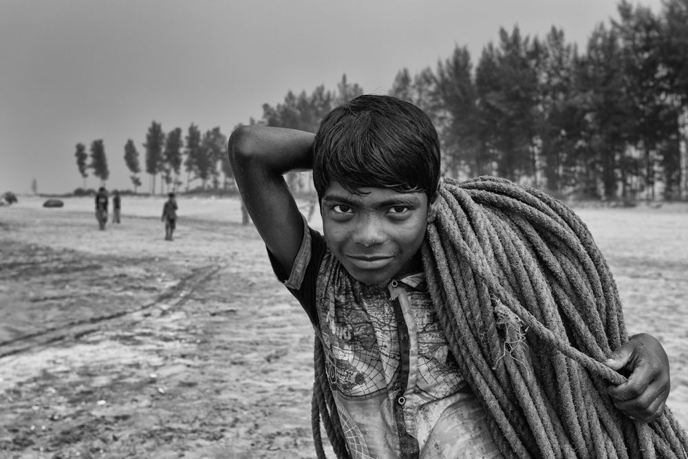 A young boy earns his daily bread working in the fishing village. One of his jobs is to help senior fishers with the daily routine of carrying a big rope on his shoulder, Bangladesh