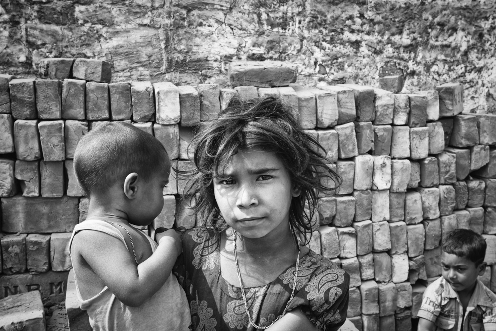 Creating a siblings bond, this young girl looks after her baby brother most days, while both their parents work in the brickfield, Bangladesh 2020