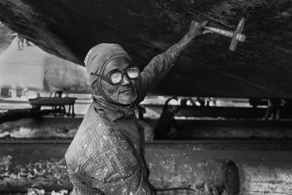 A shipyard worker removes rust from the hull of a ship, without proper ear protection at Dhaka, Bangladesh