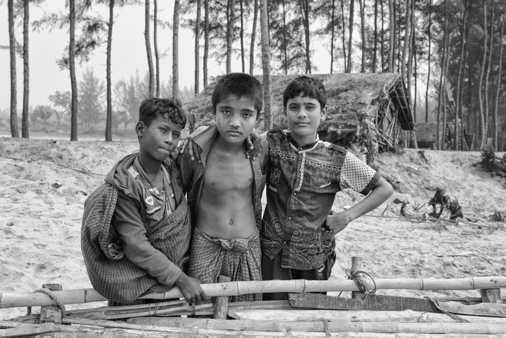 three young boys pose to the camera at the beach