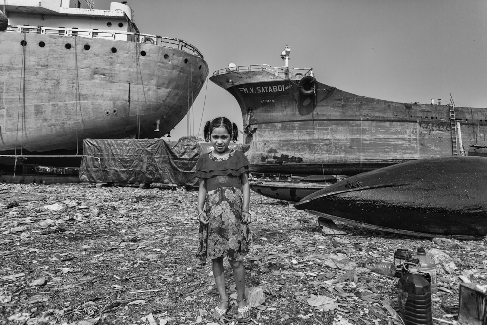 Environmental portrait of a young girl standing at the Dhaka, Bangladesh Shipyard with a backdrop of huge vessels for repairs and sale.