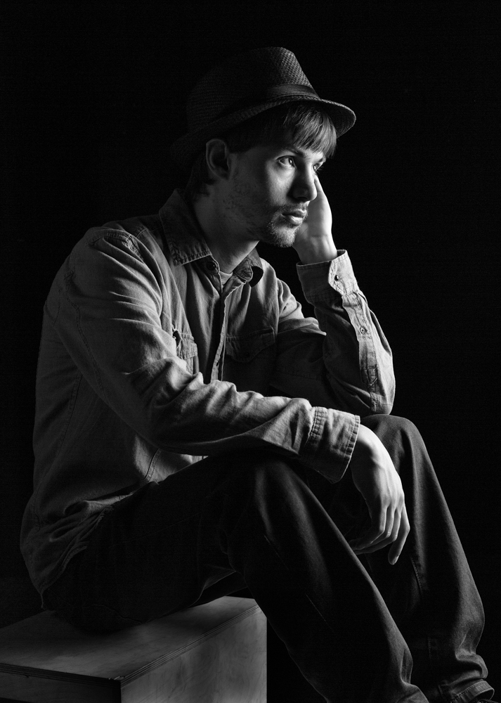 Studio lighting with the male model. Model sitting looking up and wearing a hat. Black and white portrait. Low key portrait. Minimalist lighting setup.
