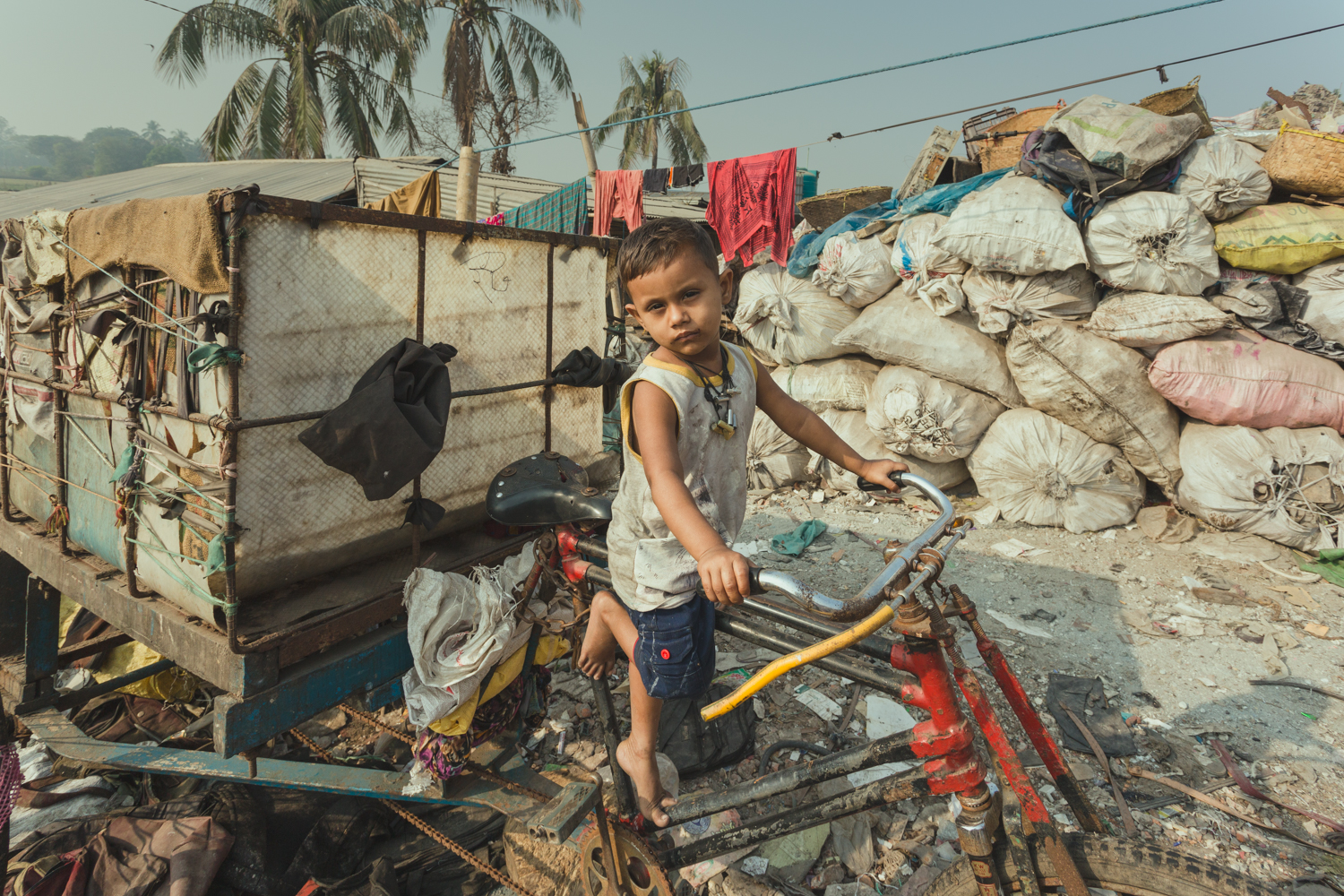 Little boy pretends to drive the rubbish collection cart in Chittagong, Bangladesh.