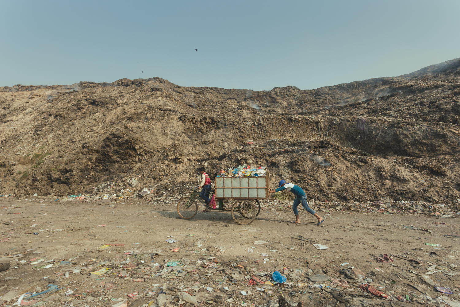 Two boys work together to transport a cart full of collected rubbish in Chittagong, Bangladesh.