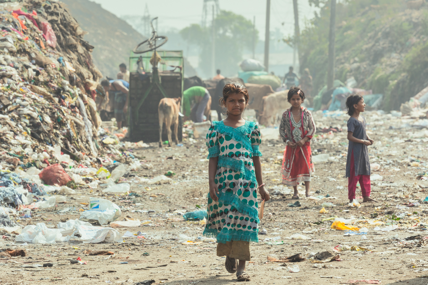 Girl standing in front of huge rubbish piles in Chittagong, Bangladesh.