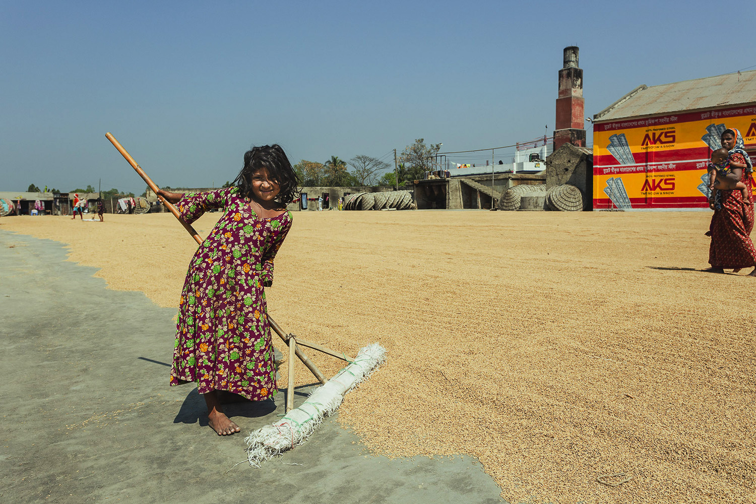 Little girl helping with the ground preparation at Dhaka, Bangladesh Rice Mills.